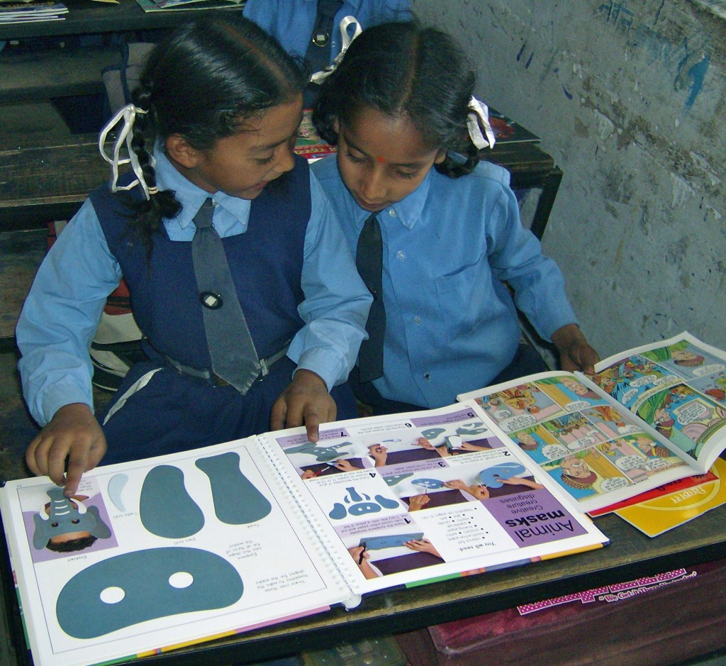 School girls giggle over their first storybooks